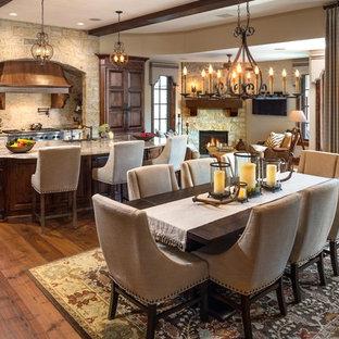 Ispirazione per una grande sala da pranzo aperta verso la cucina chic con parquet scuro, camino ad angolo e cornice del camino in pietra
