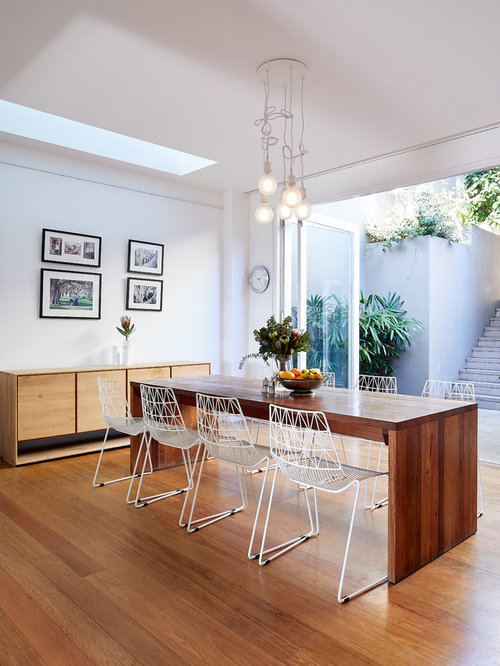 Contemporary Dining Room In Sydney With White Walls, Medium Hardwood Floors  And Brown Floor.