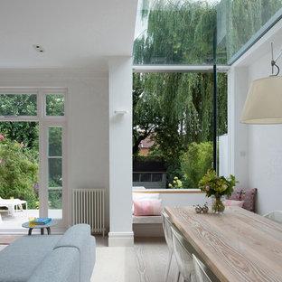 Esempio di una sala da pranzo aperta verso il soggiorno design di medie dimensioni con pareti bianche, parquet chiaro e nessun camino