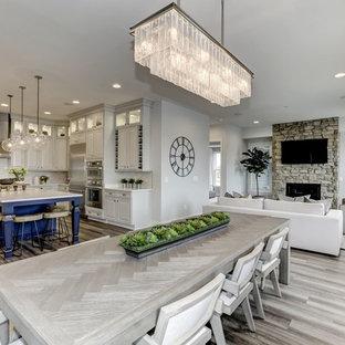 Exemple d'une salle à manger ouverte sur le salon avec un mur gris, un sol en vinyl, une cheminée standard, un manteau de cheminée en pierre et un sol gris.