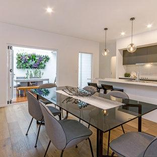Modelo de comedor de cocina contemporáneo, grande, con paredes blancas y suelo vinílico