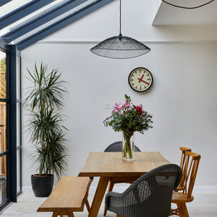 Inspiration for a medium sized contemporary dining room in Hertfordshire with white walls and beige floors.