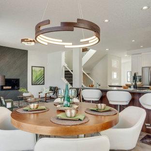 Esempio di una sala da pranzo aperta verso la cucina chic di medie dimensioni con pareti bianche, pavimento in laminato, camino classico, cornice del camino piastrellata e pavimento beige