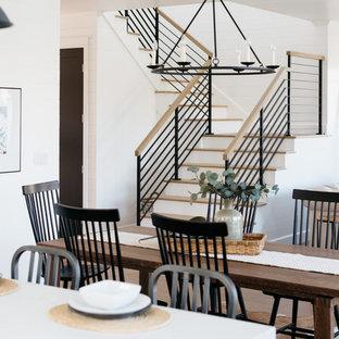 Diseño de comedor campestre, abierto, con paredes blancas, suelo de madera en tonos medios y suelo marrón