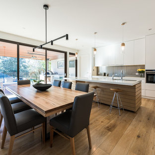 This is an example of a contemporary open plan dining in Melbourne with white walls, medium hardwood floors and brown floor.