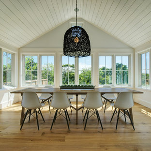 Example of a large coastal medium tone wood floor and brown floor dining room design in Boston with white walls