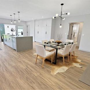 Idee per una sala da pranzo aperta verso la cucina design di medie dimensioni con pareti grigie, pavimento in vinile, camino classico, cornice del camino in cemento e pavimento marrone