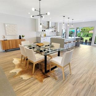 Ispirazione per una sala da pranzo aperta verso la cucina design con pareti grigie, cornice del camino in cemento, pavimento in vinile, camino classico e pavimento multicolore