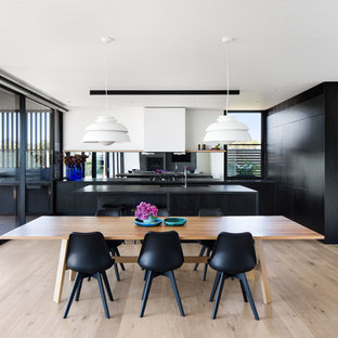 Design ideas for a contemporary kitchen/dining combo in Melbourne with white walls, light hardwood floors and beige floor.
