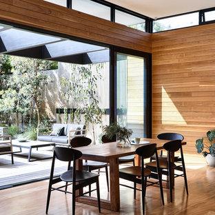 Idee per una sala da pranzo aperta verso la cucina design di medie dimensioni con pareti marroni, pavimento in legno massello medio e pavimento arancione