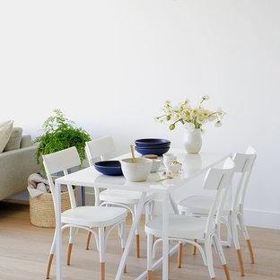 Foto de comedor escandinavo, pequeño, abierto, con paredes blancas, suelo de madera clara, chimenea de doble cara, marco de chimenea de piedra y suelo beige