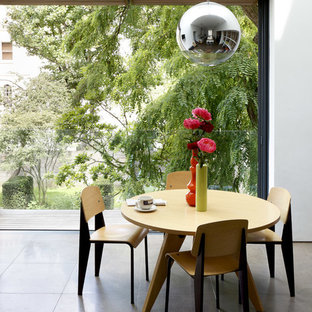 Inspiration for a medium sized contemporary dining room in London with white walls and grey floors.