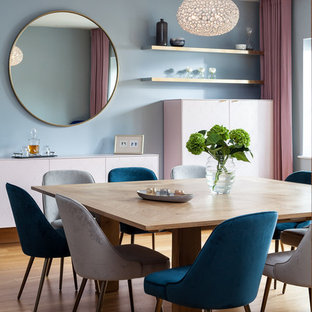 Medium sized contemporary dining room in London with blue walls, brown floors and medium hardwood flooring.