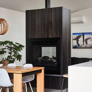 ジーロングのビーチスタイルのおしゃれなLDK (白い壁、コンクリートの床、両方向型暖炉、木材の暖炉まわり、グレーの床) の写真