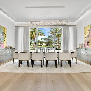 Idée de décoration pour une grand salle à manger ouverte sur le salon design avec un mur blanc, un sol en bois clair, une cheminée double-face, un manteau de cheminée en pierre, un sol beige et un plafond à caissons.