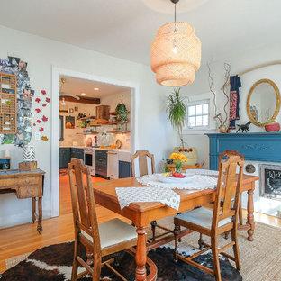 Cette photo montre une salle à manger éclectique fermée avec un mur blanc et un sol en bois clair.