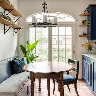 Immagine di una piccola sala da pranzo aperta verso la cucina mediterranea con pareti bianche, pavimento in terracotta, nessun camino e pavimento arancione