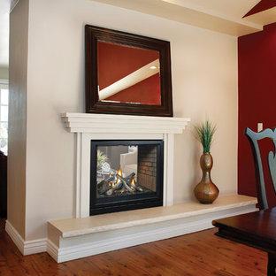 Exempel på en mellanstor modern matplats med öppen planlösning, med röda väggar, mellanmörkt trägolv, en dubbelsidig öppen spis, en spiselkrans i trä och brunt golv