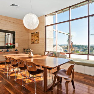 This is an example of a contemporary dining room in Other with brown walls, medium hardwood floors and brown floor.