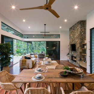 Photo of a contemporary open plan dining in Sunshine Coast with white walls, medium hardwood floors, a ribbon fireplace, a stone fireplace surround and brown floor.