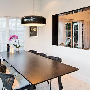 Foto di una piccola sala da pranzo aperta verso la cucina tropicale con pareti bianche, pavimento in travertino, nessun camino e pavimento nero