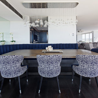 Large beach style open plan dining in Sydney with white walls, dark hardwood floors and black floor.