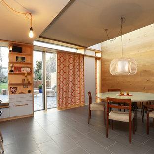 Medium sized retro dining room in London with black floors.
