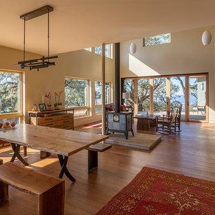Idee per una sala da pranzo aperta verso il soggiorno contemporanea di medie dimensioni con pareti beige, pavimento in legno massello medio e stufa a legna