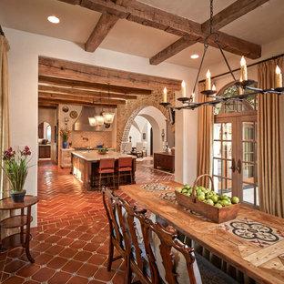 Immagine di una grande sala da pranzo aperta verso la cucina mediterranea con pareti beige, pavimento in terracotta, nessun camino e pavimento rosso