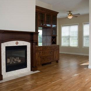 Imagen de comedor clásico, pequeño, abierto, con paredes beige, suelo de madera en tonos medios, chimenea tradicional y marco de chimenea de piedra