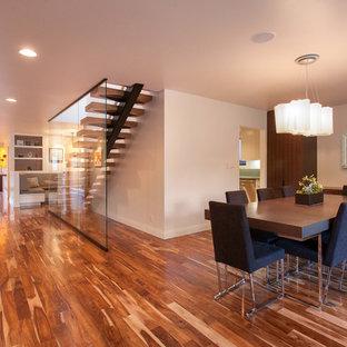Идея дизайна: большая гостиная-столовая в современном стиле с бежевыми стенами, паркетным полом среднего тона, угловым камином, фасадом камина из камня и коричневым полом