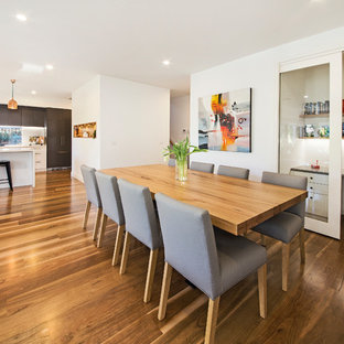 This is an example of a contemporary open plan dining in Melbourne with white walls and medium hardwood floors.