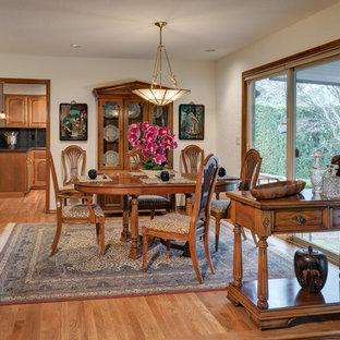 Geschlossenes, Mittelgroßes Tropenstil Esszimmer mit weißer Wandfarbe, braunem Holzboden, Kamin, Kaminsims aus Backstein und braunem Boden in Portland