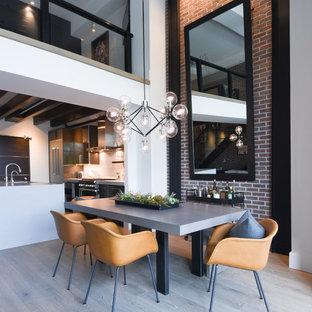 Immagine di una sala da pranzo aperta verso la cucina industriale con pareti bianche e pavimento grigio