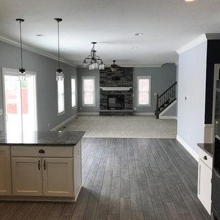 Idée de décoration pour une salle à manger ouverte sur le salon de taille moyenne avec un mur gris, un sol en vinyl, une cheminée standard, un manteau de cheminée en brique et un sol gris.