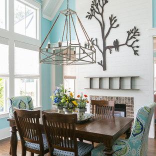 Immagine di una sala da pranzo costiera con pareti blu, parquet scuro, pavimento marrone, camino bifacciale e cornice del camino in mattoni