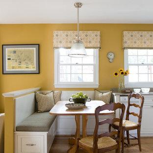 Modelo de comedor de cocina clásico, de tamaño medio, sin chimenea, con paredes amarillas, suelo de madera en tonos medios y suelo marrón
