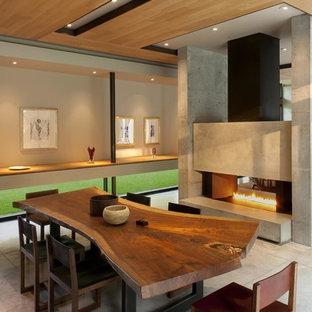 Modelo de comedor contemporáneo, abierto, con paredes beige, suelo de cemento, chimenea de doble cara y marco de chimenea de hormigón
