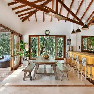 Ejemplo de comedor machihembrado y abovedado, tropical, abierto, con paredes blancas y suelo beige