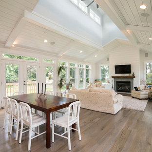 Imagen de comedor campestre, grande, con paredes blancas y suelo de madera en tonos medios