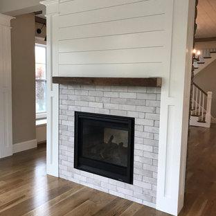 На фото: класса люкс гостиные-столовые среднего размера в стиле кантри с серыми стенами, двусторонним камином и фасадом камина из кирпича