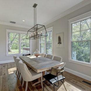 Foto di una sala da pranzo aperta verso la cucina minimalista con parquet chiaro e pareti grigie