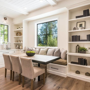 Example of a transitional medium tone wood floor and brown floor dining room design in Los Angeles with white walls