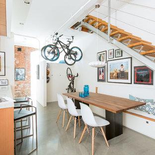 Esempio di una grande sala da pranzo aperta verso la cucina industriale con pavimento in cemento, pareti bianche e pavimento grigio