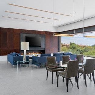 Idee per una grande sala da pranzo aperta verso il soggiorno design con pareti bianche, pavimento in gres porcellanato, camino lineare Ribbon, cornice del camino in metallo e pavimento bianco