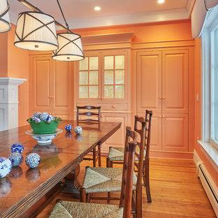 Immagine di una sala da pranzo aperta verso il soggiorno classica di medie dimensioni con pareti arancioni, pavimento in legno massello medio, camino classico, cornice del camino piastrellata e pavimento marrone