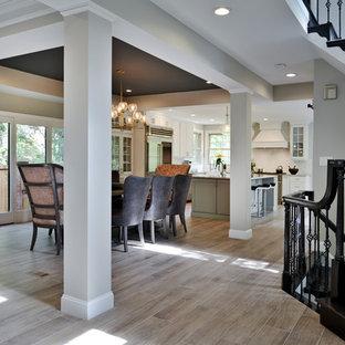 Immagine di una grande sala da pranzo aperta verso la cucina classica con pavimento in laminato e pavimento marrone