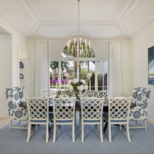 Inspiration for a large tropical separate dining room in Miami with white walls, no fireplace, beige floor and ceramic floors.