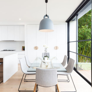 Inspiration for a scandinavian kitchen/dining combo in Melbourne with white walls, light hardwood floors and beige floor.