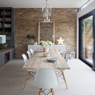 Modelo de comedor campestre, grande, abierto, sin chimenea, con suelo de baldosas de porcelana, paredes blancas y suelo gris
